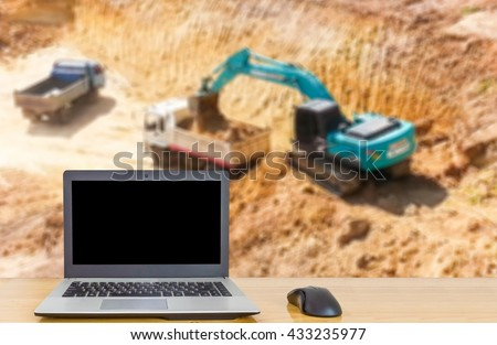 Computer on the table, blur image of machines are working in mines as background. - stock photo