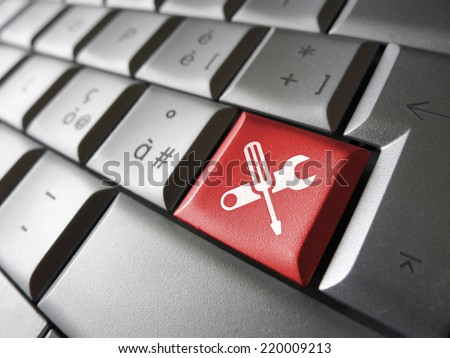 Computer repair service concept with work tools icons and symbol on a red laptop computer key for website and online business. - stock photo