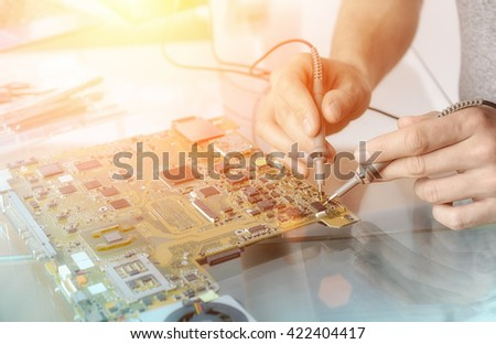 Computer repair service; hands of male tech testing motherboard - stock photo