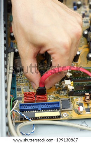 computer repairman attach the hard disk drive cable to motherboard - stock photo