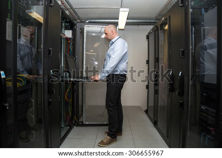 Computer specialist working on servers in a server room, looking at computer display in one of the cabinets - stock photo