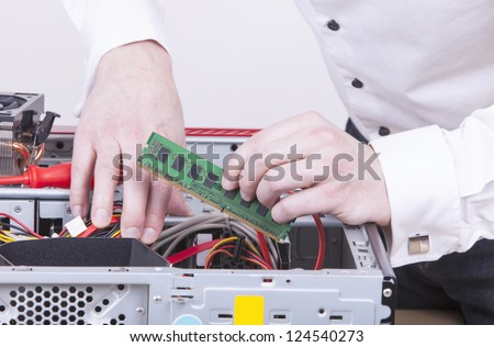 computer support engineer upgrading the RAM ( internal Memory ) chip of an office computer. Studio shot on a white background. - stock photo