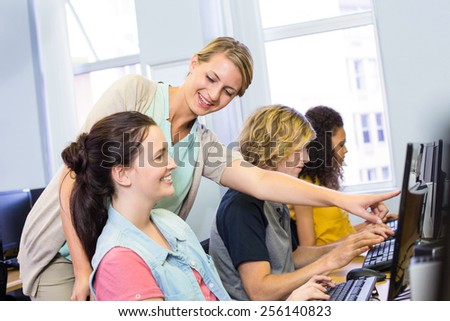 Computer teacher helping female students in her class - stock photo