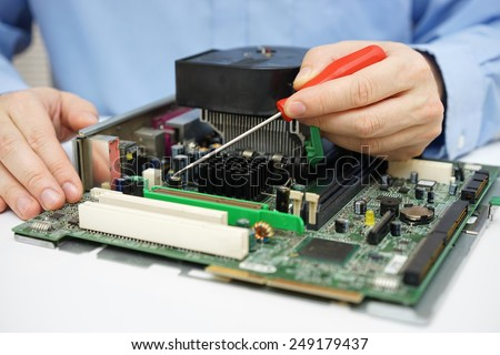 Computer  technician is checking computer motherboard - stock photo
