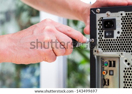 Computer technician uses screwdriver to open hardware - stock photo