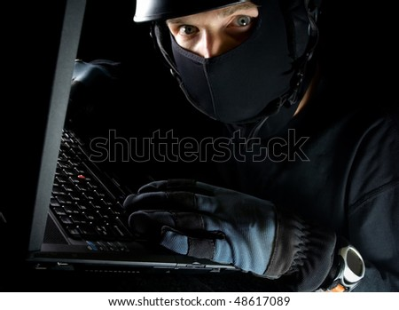 Computer theft on laptop at night, internet crime online - stock photo