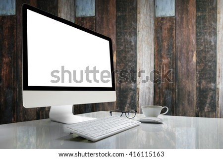 Computer with blank screen on table with blur background of vintage wood wall. - stock photo