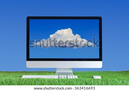 computer with cloud in the screen on green grass and blue sky background - stock photo
