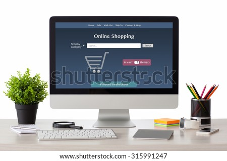 computer with onlain shopping site on the screen stands on the table in the office with phone and watch - stock photo