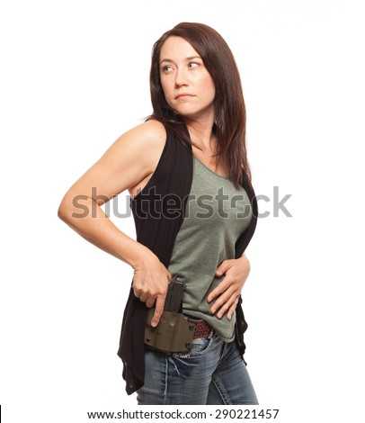 CONCEALED CARRY AND PERSONAL DEFENSE | Woman Practicing Gun Safety with hand on gun in holster, looking over her shoulder | Female shooter holding handgun against white background.  - stock photo