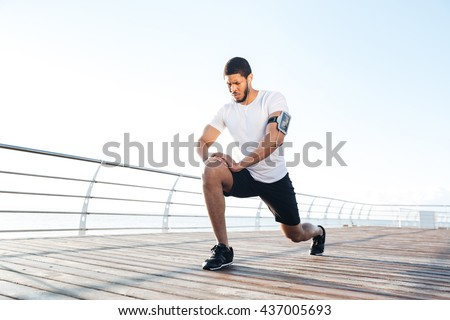 Concentrated african american sportsman warming up and stretching legs on pier - stock photo