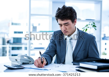 Concentrated asian businessman writing something is his office - stock photo