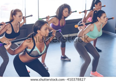 Concentrated at their workout. Beautiful young women with perfect bodies in sportswear exercising with barre while standing in front of window at gym - stock photo