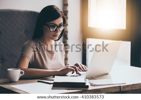 Concentrated at work. Young beautiful woman using her laptop while sitting in chair at her working place - stock photo