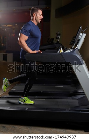 Concentrated athletic man training on a running machine in a fitness center .Low light  - stock photo