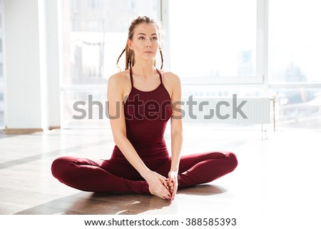 Concentrated attractive young woman stretching and doing yoga in studio - stock photo