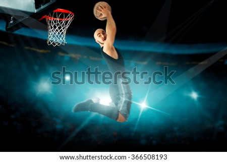 Concentrated basketball player in black jersey makes reverse slam dunk. . Basketball game. Sportsman plays basketball. - stock photo