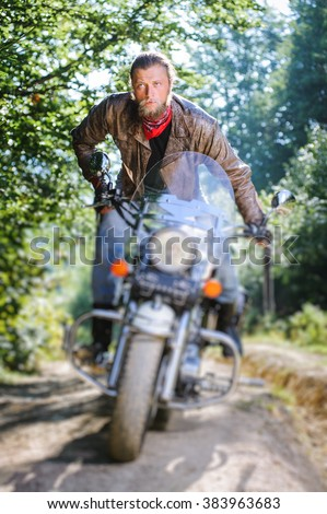Concentrated biker with beard driving his cruiser motorcycle in the forest. Man is wearing leather jacket and blue jeans. Tilt shift lens blur effect - stock photo