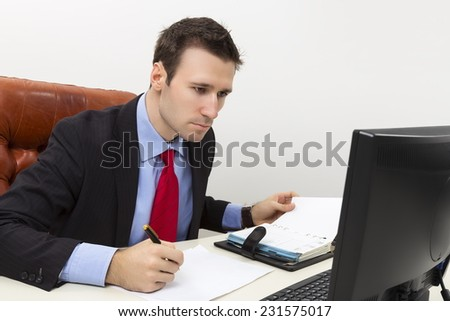 Concentrated business man analyzing data on computer display and filling a paper document. - stock photo