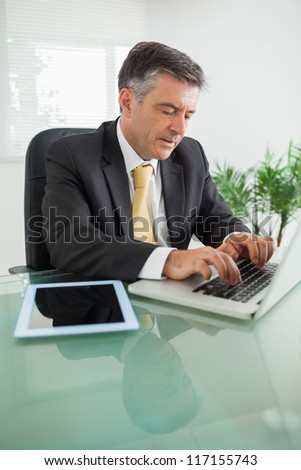 Concentrated business man working on laptop on a table in an office - stock photo