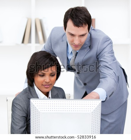 Concentrated business partners working at a computer in the office - stock photo