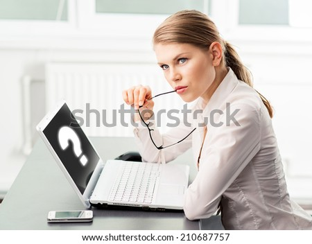 Concentrated business woman finding problem solution sitting in the office. Young female project manager searching answer for question.  - stock photo