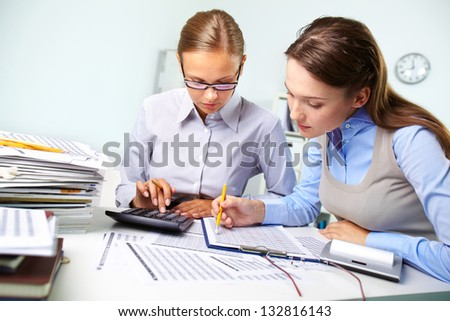 Concentrated business women reviewing accounting report - stock photo