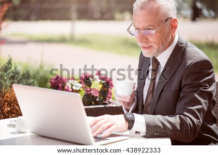 Concentrated businessman sitting at the table - stock photo