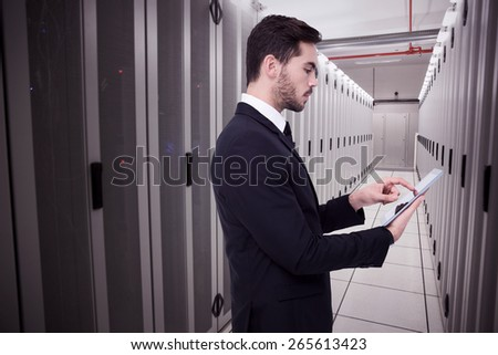 Concentrated businessman touching his tablet against data center - stock photo