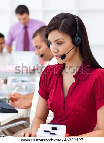 Concentrated  Businesswoman using headset in a call center - stock photo