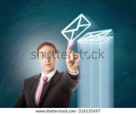 Concentrated, but overworked corporate man finishing stacking emails into a tall pile of countless virtual documents. Business concept for overtime, overload, overwhelming task, and work discipline. - stock photo