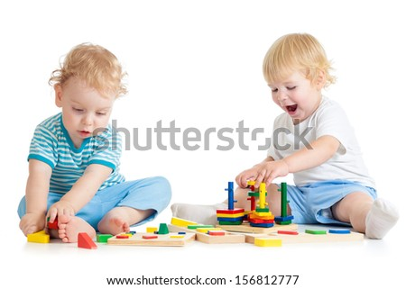 Concentrated child playing logical education toys with great interest on white background - stock photo