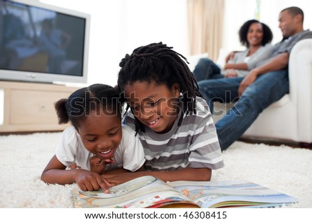 Concentrated children reading a book lying on the floor - stock photo