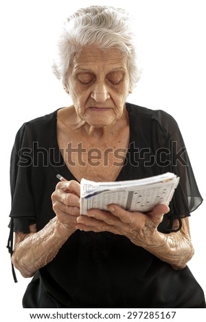 Concentrated elderly doing crossword . - stock photo