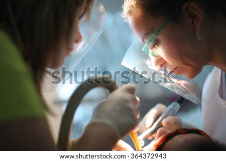 Concentrated face of a female dentist at work  - stock photo