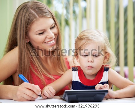 Concentrated girl calculating family bills sitting at the desk with her mom. Budget planning concept. - stock photo