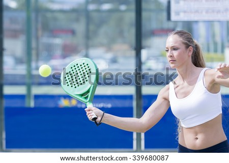 concentrated girl playing a paddle match is ready to hit the ball in an artificial grass court - focus on the face - stock photo