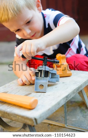 Concentrated little boy is playing in carpenter - stock photo