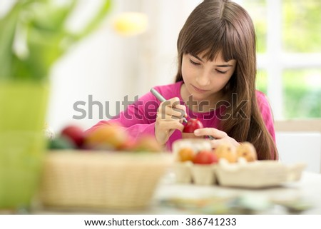 Concentrated little girl painting Easter eggs - stock photo