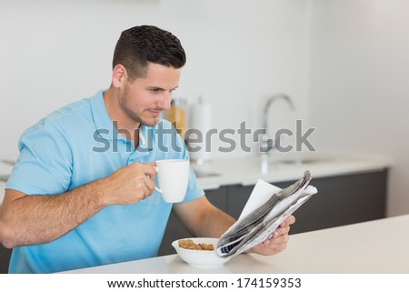 Concentrated man reading newspaper while drinking coffee at table in kitchen - stock photo