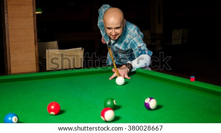 Concentrated man try to hit the cue ball on pool table. Pool billiard game. American pool billiard. Billiard sport concept. - stock photo