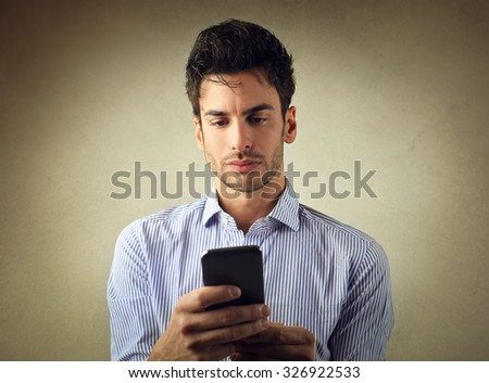 Concentrated man using a smart phone - stock photo