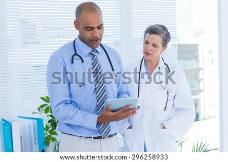 Concentrated medical colleagues with tablet computer in the hospital - stock photo