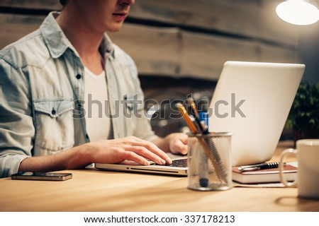 Concentrated on work. Close-up of confident young man working late while sitting at his working place  - stock photo