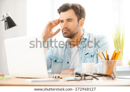 Concentrated on work. Handsome young man working on laptop while sitting at his working place - stock photo