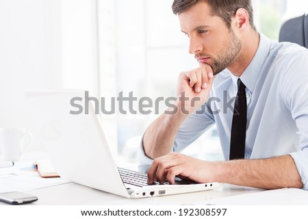 Concentrated on work. Side view of thoughtful young man in formal wear looking at laptop and holding hand on chin while sitting at his working place - stock photo