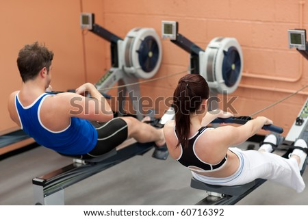 Concentrated people using a rower in a fitness center - stock photo