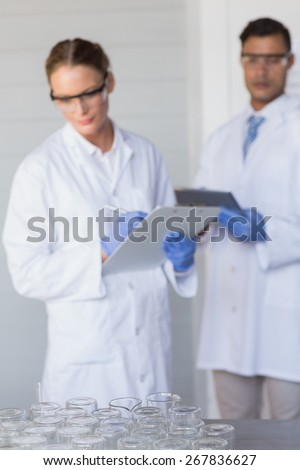 Concentrated scientists looking at beakers in laboratory - stock photo