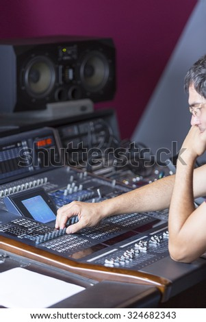 concentrated sound professional adjusting a sound mixing desk at the recording studio - focus on the right hand - stock photo