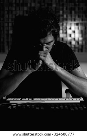 concentrated sound technician sitting on a recording room adjusting a sound mixing desk - focus on the face - stock photo